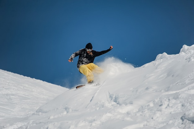 Freeride snowboarder at jump in high mountains at sunny day