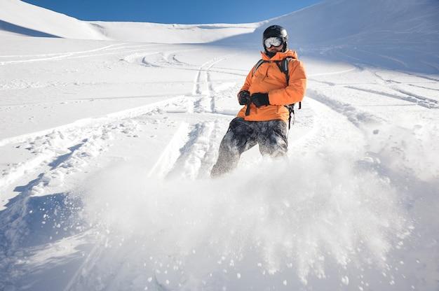 Freeride snowboarder sliding down the mountain slope