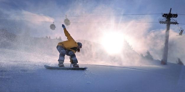 Freerider 스노우보더 소녀는 역광 태양 아래 산에서 미끄러집니다.