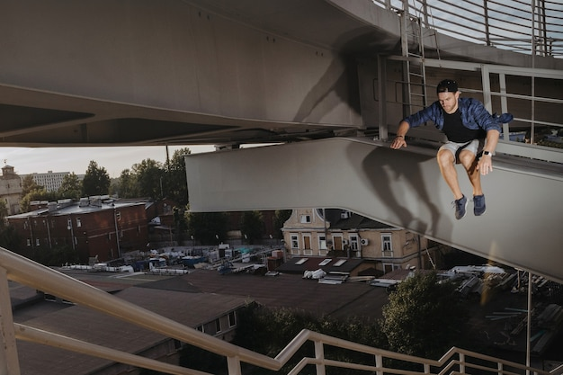 Freerun athlete doing scary jump from high bridge