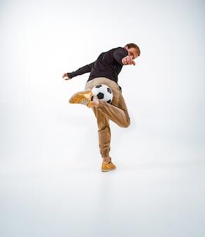 Портрет вентилятора с мячом на фоне серой студии. freestile