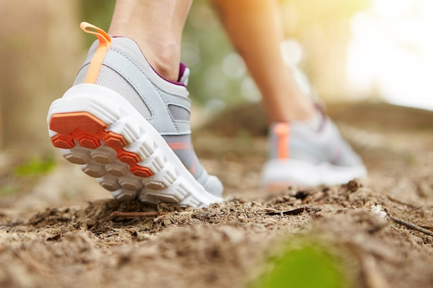 Freeze action closeup of young woman walking or running on trail in forest or park in summer nature outdoors. athletic girl wearing sport shoes, exercising on footpath.