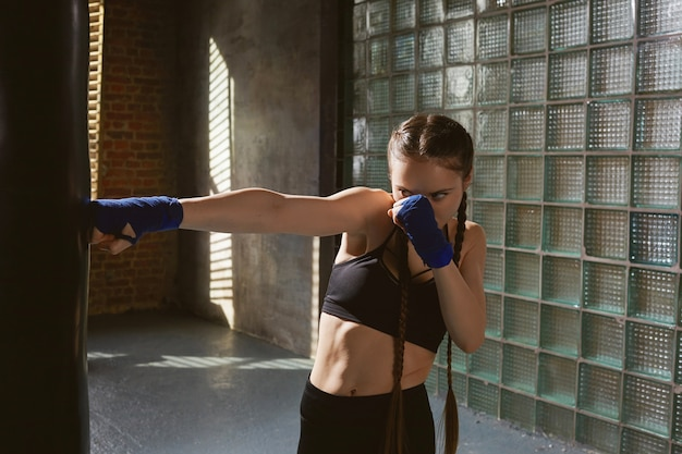 완벽한 근육질의 몸매가 체육관에서 혼자 운동하는 놀라운 집중 젊은 여성 전투기의 액션 초상화를 고정