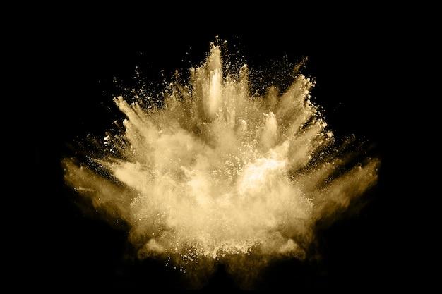 Freeze motion of golden powder exploding, isolated on black background