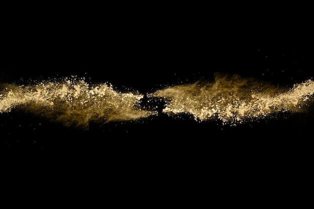 Заморозить движение взрывающаяся золотой порошок, изолированных на черном фоне