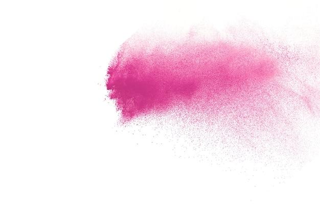 白で爆発するピンク色の粉末の凍結運動