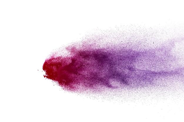 白い背景で爆発する紫色の粉末の凍結運動。