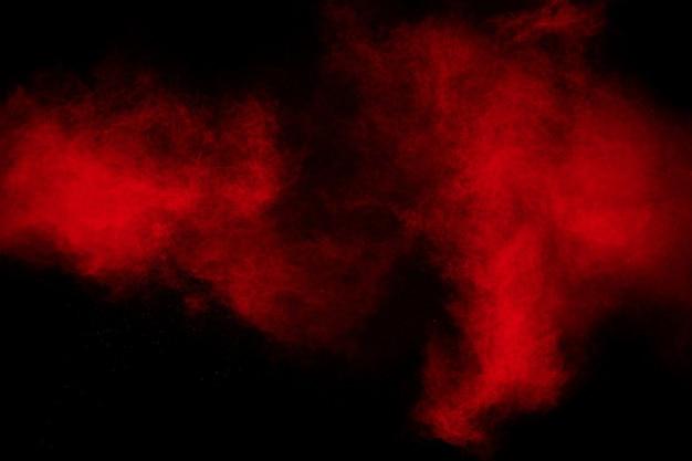 Заморозьте движение брызг красных частиц пыли.