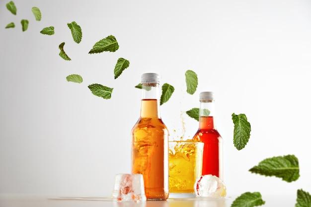 Spruzzata congelata in aria di cocktail dal cubetto di ghiaccio in vetro con gustosa bevanda gialla tra due bottiglie trasparenti sigillate senza etichetta con aperol e sidro