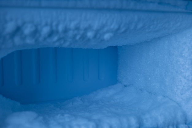 The freezer compartment of the refrigerator has a lot of ice on it.