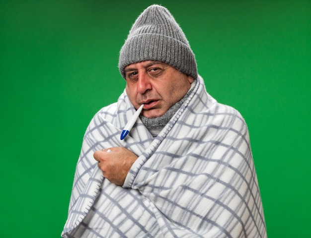 Freezing adult ill caucasian man with scarf around neck wearing winter hat wrapped in plaid holding thermometer in his mouth isolated on green wall with copy space