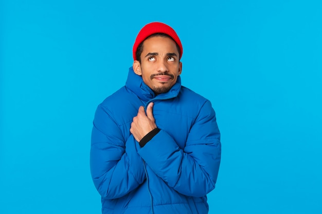 Freezing cold, winter weather concept. bothered and displeased young african-american male student in red hipster hat, padded jacket, wrap himself tight and looking up, trembling from low temprature