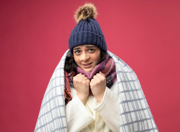 Congelamento freddo giovane indoeuropea ragazza malata che indossa abito invernale cappello e sciarpa avvolti in plaid mantenendo i pugni sotto il mento con intonaco sul naso isolato sulla parete cremisi
