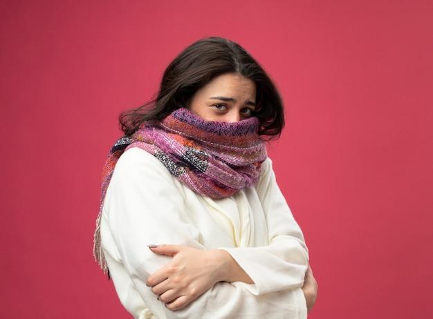 Giovane donna ammalata caucasica fredda che copre la bocca con la sciarpa