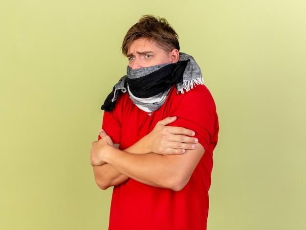 Congelamento freddo giovane uomo malato bello biondo che indossa sciarpa tenendo le mani incrociate sulle braccia guardando dritto isolato sulla parete verde oliva con lo spazio della copia