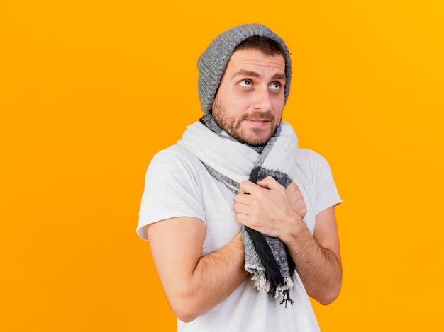 冬の帽子と黄色で隔離のスカーフを身に着けている凍てつく寒い若い病気の男