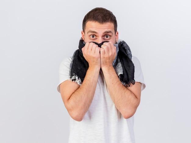 Il giovane uomo malato freddo freddo che porta il cappello e la sciarpa di inverno ha coperto il fronte con la sciarpa isolata su bianco