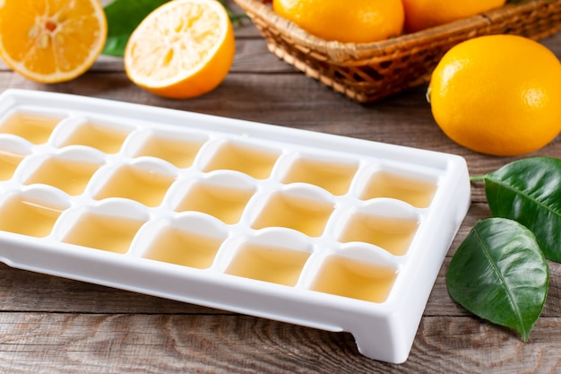 Freezing lemon juice in cubes in a tray with fresh lemons on a wooden table