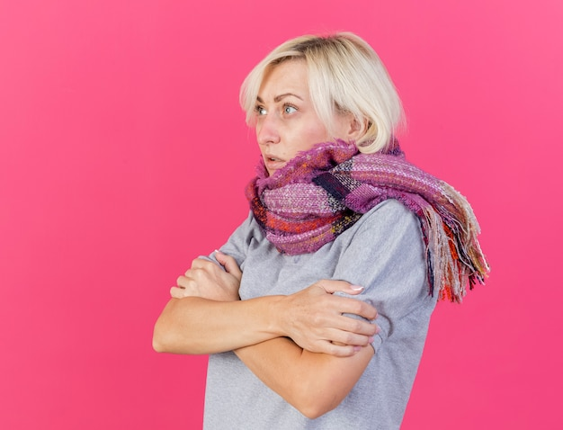 스카프를 착용하는 젊은 금발의 아픈 슬라브 여자 동결 분홍색 측면을보고 팔 보유