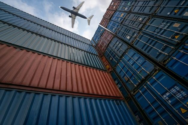 海外の輸送コンテナの上を飛ぶ貨物飛行機