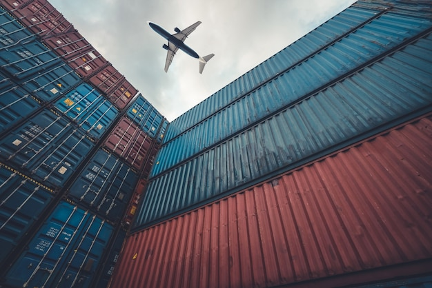 Freight airplane flying above overseas shipping container