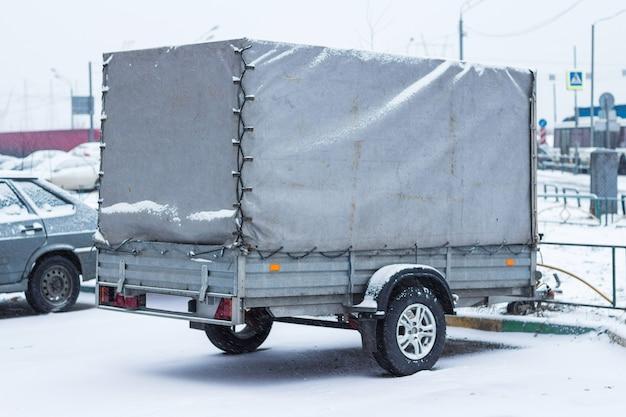 雪の中の春先の駐車場での貨物トレーラー