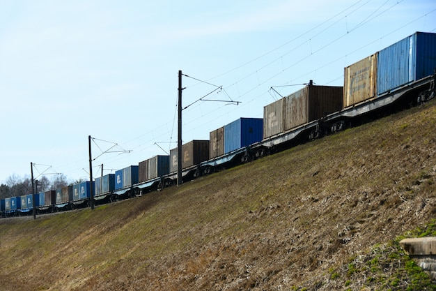 Freight train cars travel by rail on a slope