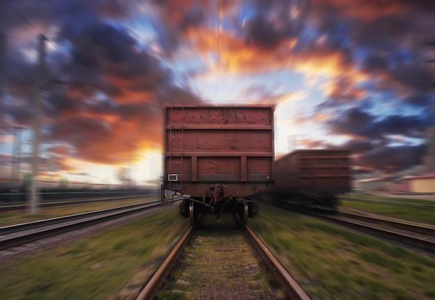 雲のある夕焼け空を背景にぼかし効果のある貨物列車が動いています。