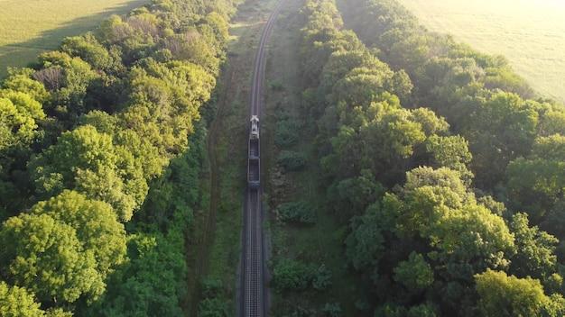 空の車が2台ある貨物列車、線路上のトラクターが町を出て行きます。