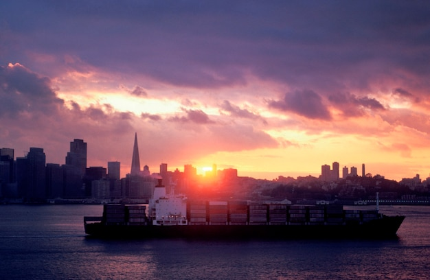 Freighter of containers with cityscape and sunset in background