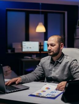 Frelancer работает сверхурочно на корпоративном рабочем месте, глядя на ноутбук, сидя за столом. бородатый предприниматель вечером осматривает офис, чтобы закончить срок.
