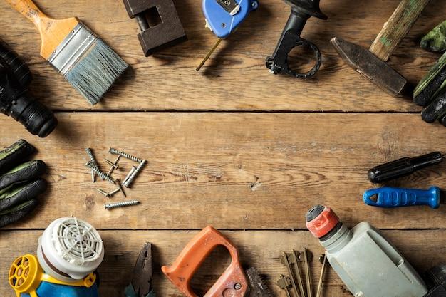 나무 배경 상단 보기에 있는 다양한 오래된 수제 도구 세트용 프레임