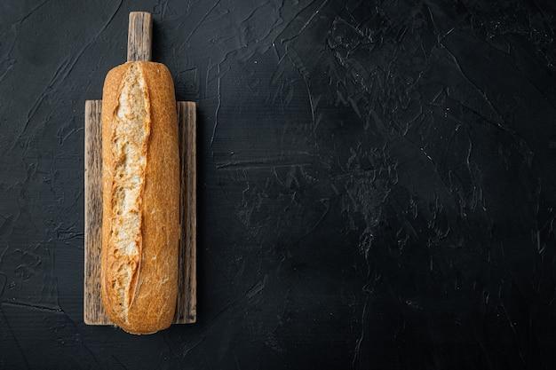 검정색 배경에 구운 프랑스 바게트 빵, 텍스트 복사 공간이 있는 평면도