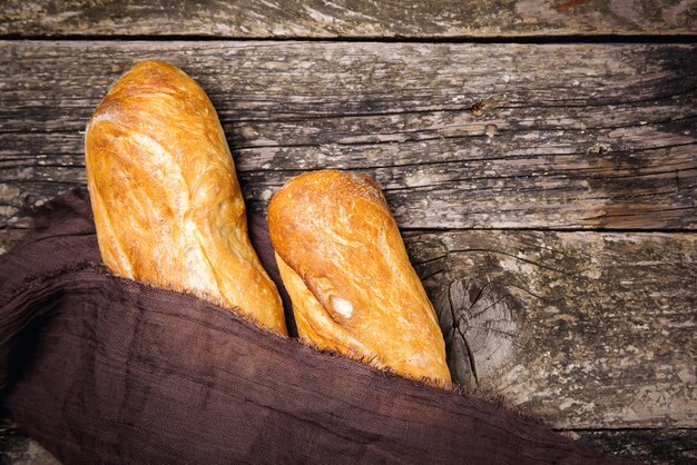 Французский хлеб багет на старом деревенском деревянном фоне
