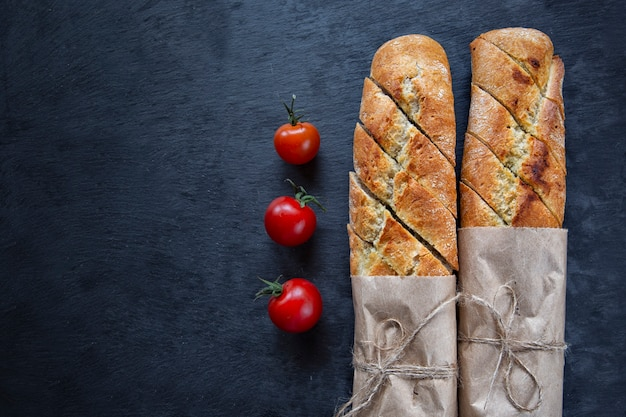 French baguette and cherry tomatoes on a dark background