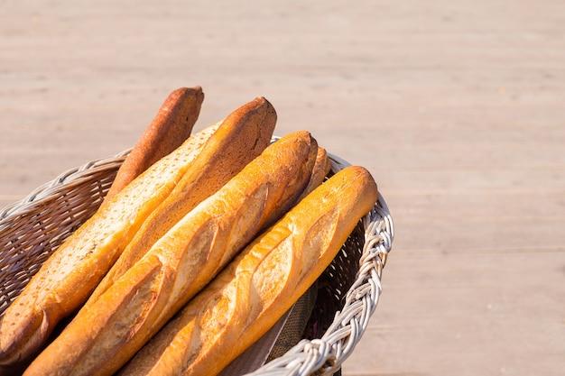 茶色の背景に素朴な木製バスケットのフランスパン