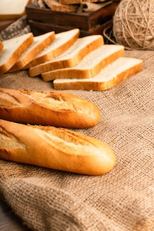 French baguette with slices of bread on tablecloth