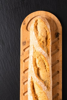 French baguette on wooden board and black slate board with copy space