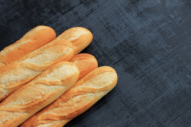 French baguettes on black wooden background.