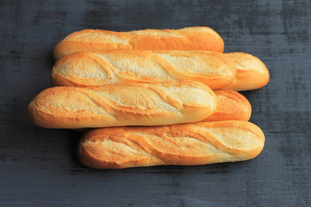French baguettes on black wooden background