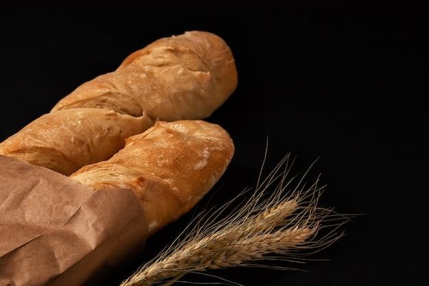紙袋に入ったフランスパンと暗いテーブルトップに小麦の穂。上からの眺め
