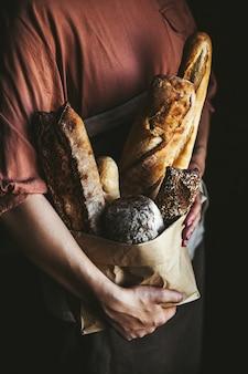 검정색 배경에 여성 손에 프랑스 바게트. 수제 베이킹
