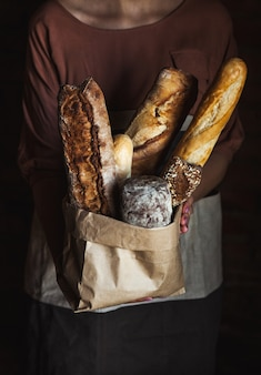 黒の背景に女性の手でフランスパン。自家製ベーキング