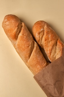 French baguettes in a paper bag and ears of wheat on a light table top. view from above