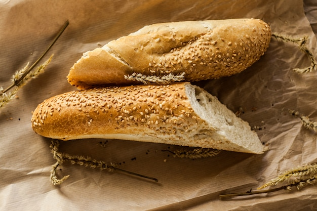 French baguettes with sesame seed on a paper bag lie on a wooden table.