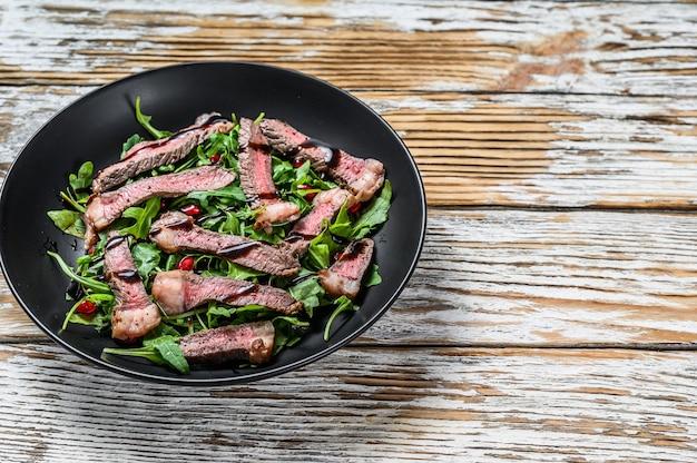 Французский стейк из перца из говядины с салатом из листьев рукколы.