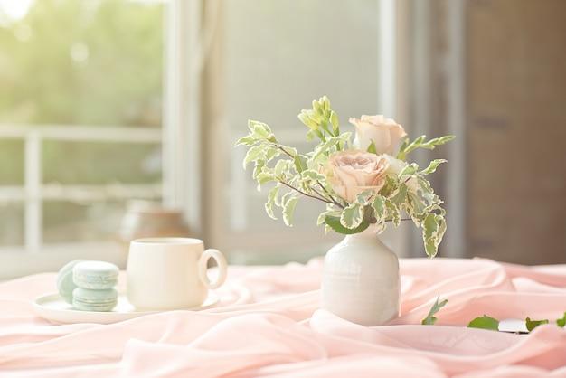 꽃 장미와 녹색 분홍색 식탁보 흰색 꽃병 나무 테이블에 프랑스 블루 마카롱 접시와 커피 컵 서