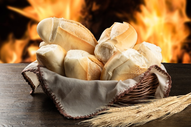 French breads in basket with blurred fire background.