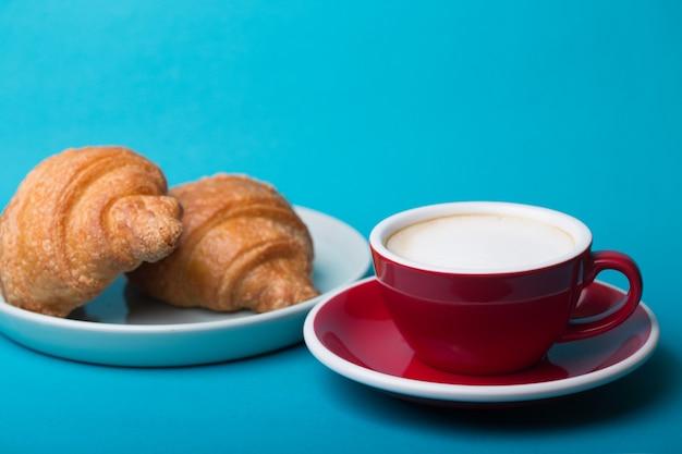 フランスの朝食。青い背景にクロワッサンと美しいコーヒー赤いカップカプチーノ