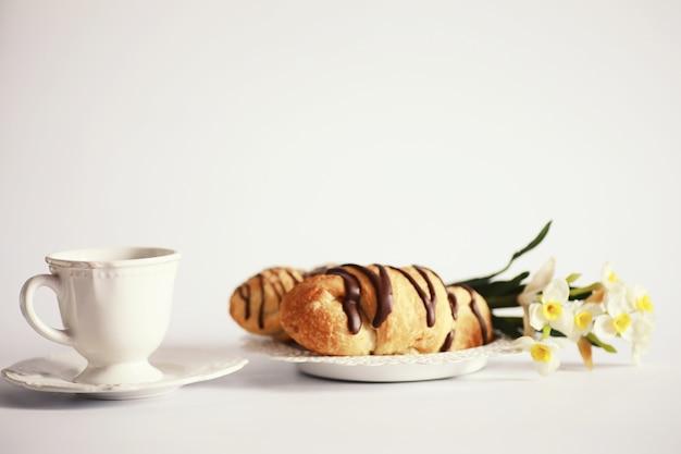 테이블에 프랑스 아침 식사입니다. 초콜릿을 곁들인 커피 크루아상과 크림을 곁들인 디캔터. 신선한 패스트리와 카페인이 없는 커피.